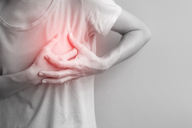 Woman hands holding chest ache. breast cancer, angina disease and symptom heart attack disease
