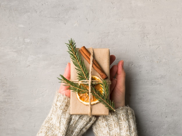 Woman hands holding christmas gift box in gray concrete