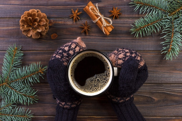 Woman hands holding coffee mug. holiday decorations, christmas background