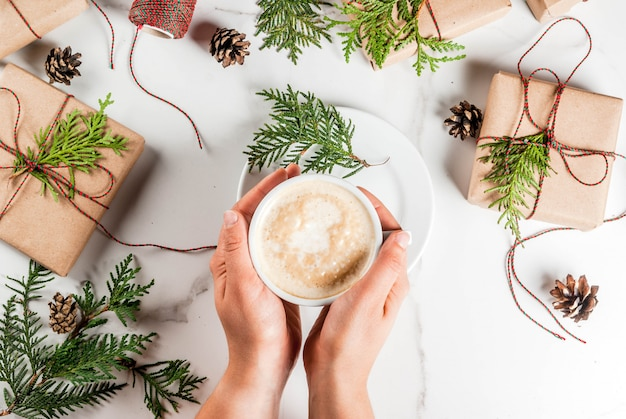 Woman hands holding coffee mug, with christmas gift or present box wrapped in kraft paper, decorated with christmas tree branches, pine cones, red berries, on white marble table top view
