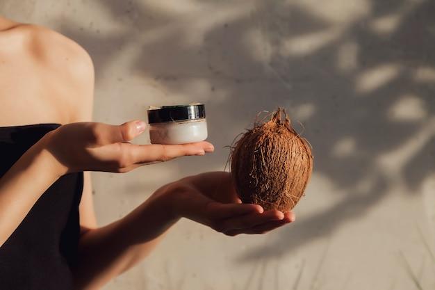 顔の皮膚に適用するための化粧品クリームとココナッツを保持している女性の手。女性は葉から日陰で壁の背景にローションを保持します。健康的なライフスタイル、spa、セルフケアの広告コンセプト