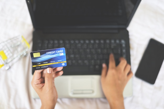 Woman hands holding credit card and using laptop for online shopping with shopping cart