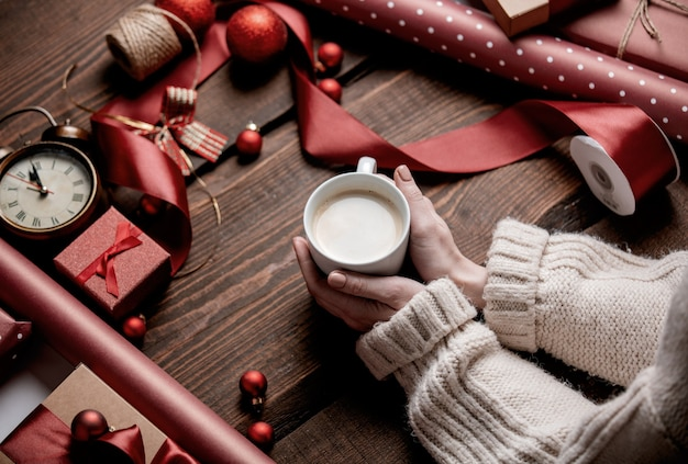 Woman hands holding cup of coffee on wooden table in wrapping time
