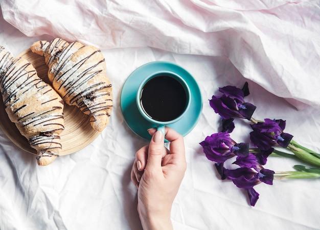 ベッドで一杯のコーヒーを保持している女性の手。美しい花とブレスレット付きの時計