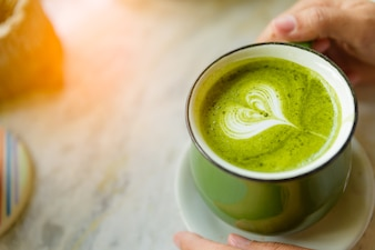 Woman hands holding cup of hot green tea with heart shaped.