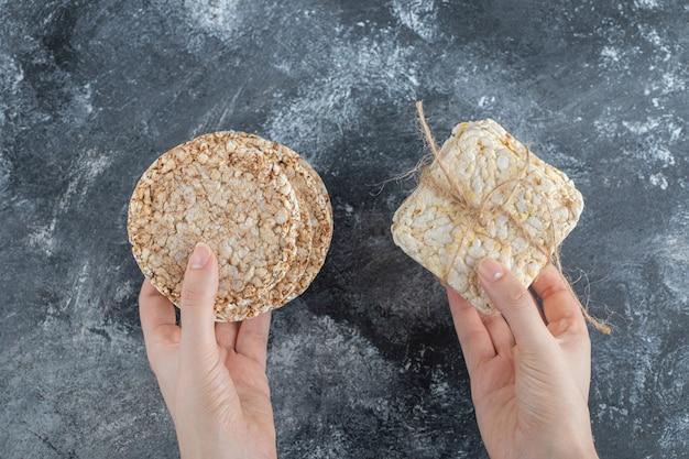 여자 손에 맛있는 숨이 차서 쌀 빵을 들고입니다.