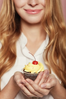 Woman hands holding a delicious yummy cupcake