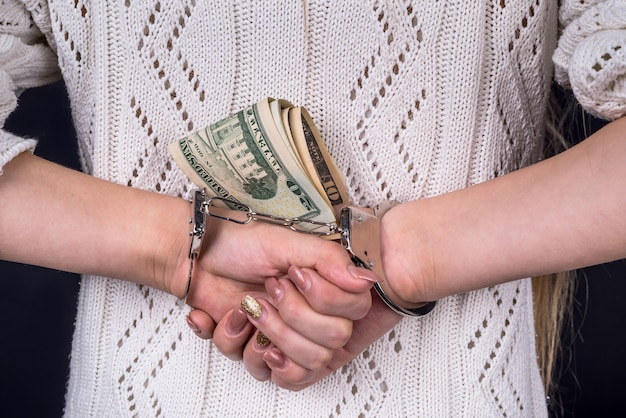 Woman hands holding dollar banknotes in handcuffs behind back