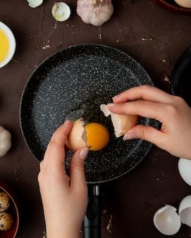 あずき色のテーブルの上のフライパンで卵黄と卵殻を保持している女性の手