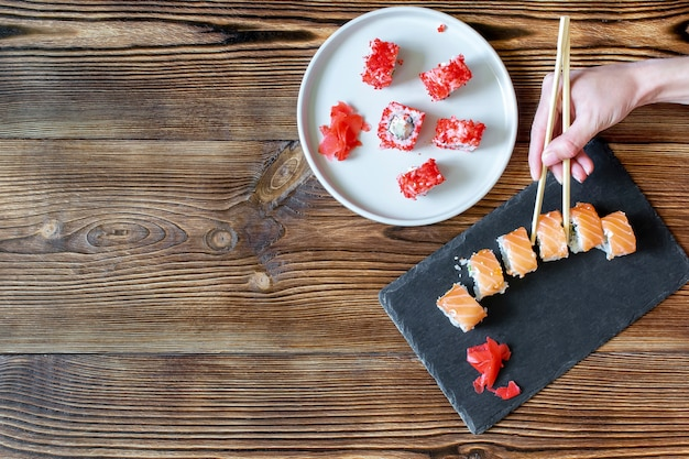 Woman hands holding fish sushi rolls with salmon, red caviar with chopsticks on gray black ceramic serving plate on wooden rustic background close up. seafood, food service from restaurant concept.