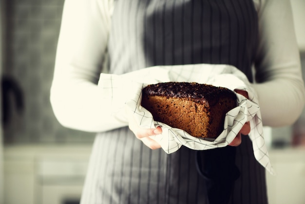 Woman hands holding freshly baked bread.