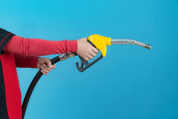 Woman hands holding fuel nozzle isolated on blue background