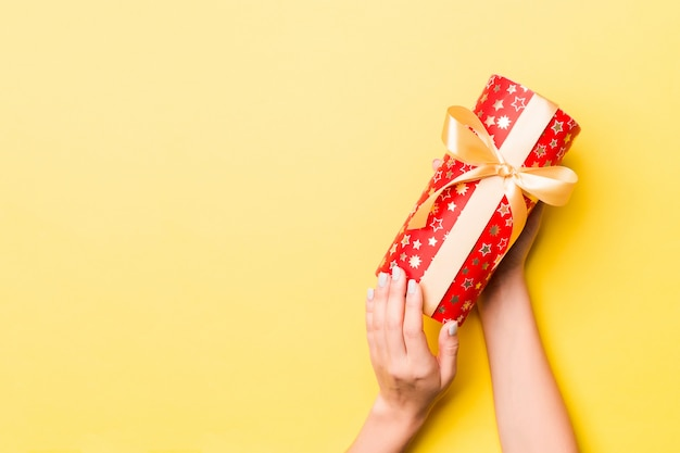 Woman hands holding gift box on colored background
