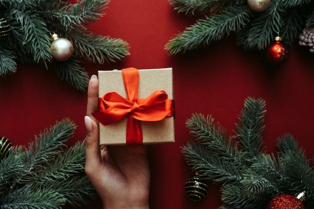 여자 손에 선물 상자를 들고입니다. 전나무 나무와 휴일 장식.