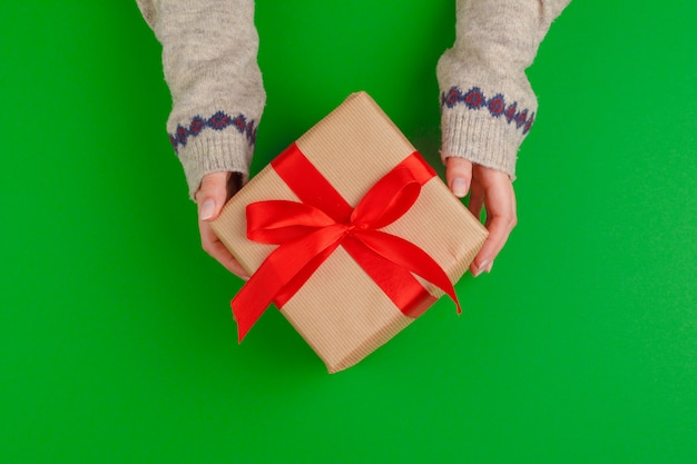Woman hands holding gift box on green background