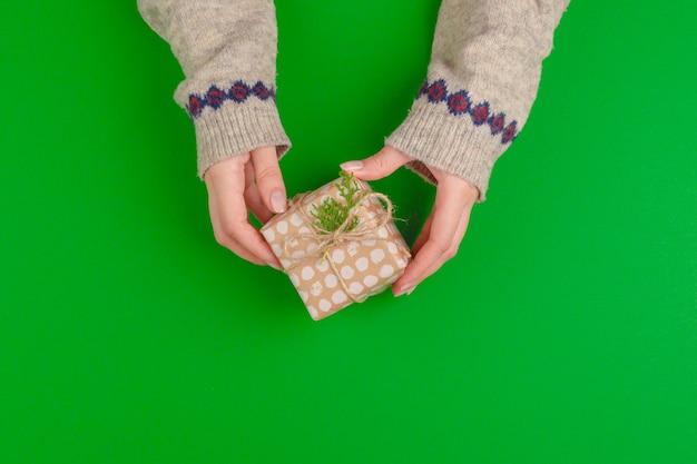 Женщина руки, держа подарочную коробку на зеленом фоне