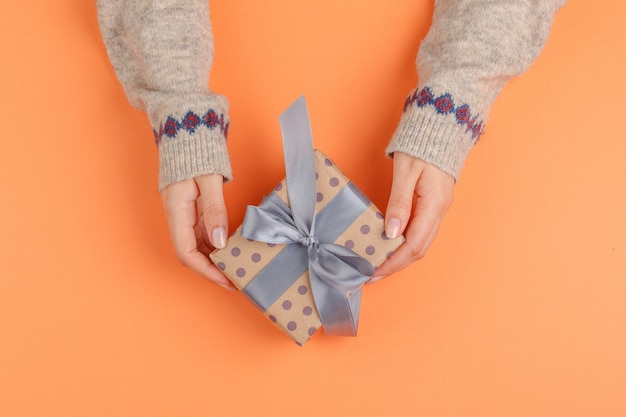 Woman hands holding gift box on orange