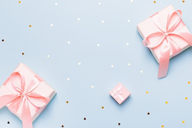 Woman hands holding gift box in pink color on pastel blue background with heart shape confetti, copyspace. valentine's day greeting card in trendy colors, happy valentine day background, overhead