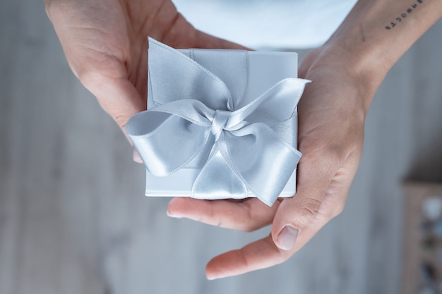 Woman hands holding gift box with white bow, close-up