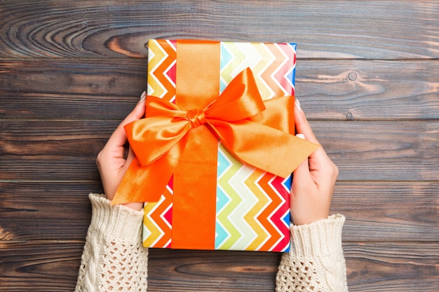 Woman hands holding gift box on wooden background