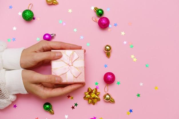 クリスマスボールと色とりどりのキャンディースター、ピンクの背景にリボンで飾られたギフトを保持している女性の手、コピースペース。フラットレイ、手とギフトボックス、上面図。クリスマスのコンセプト。