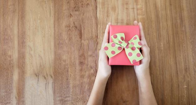 木製のテーブルに贈り物をする女性の手