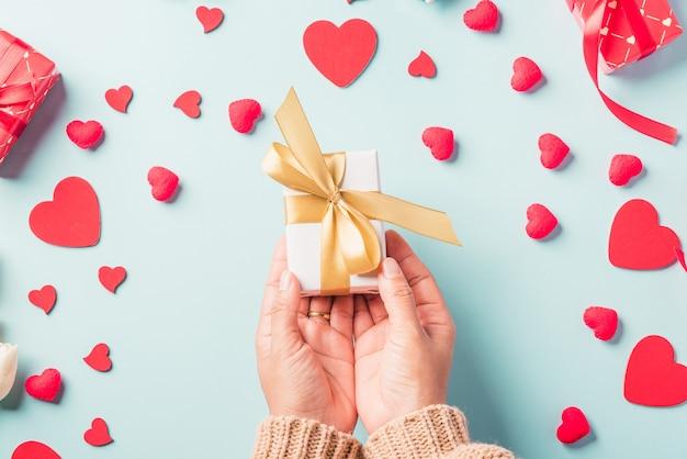Женщина руки держит подарочную или настоящую коробку, украшенную и красное сердце