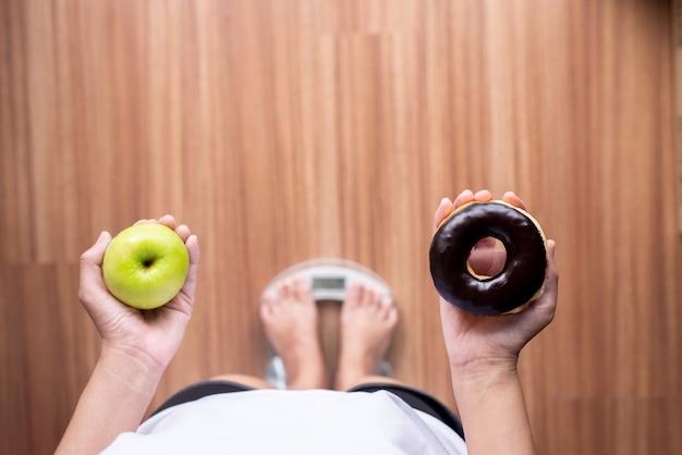 체중계에 서서 녹색 사과와 구운 초콜릿 도넛을 들고 있는 여성의 손, 건강한 식단, 다이어트 개념