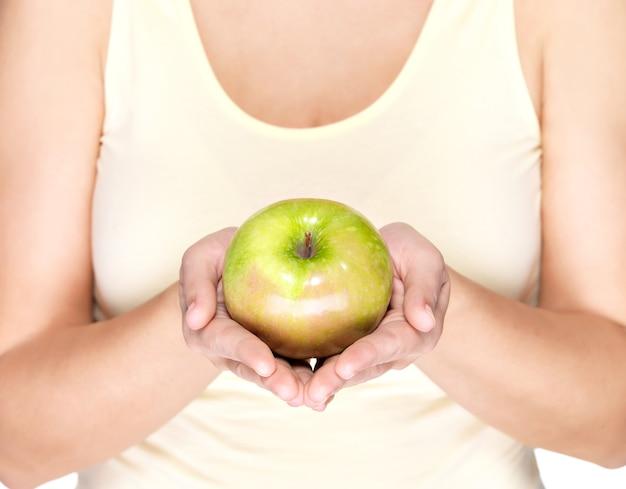 Mani della donna che tengono mela verde - isolata su bianco.