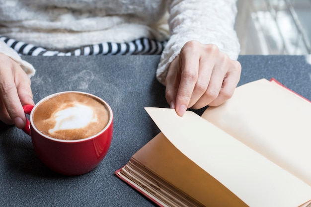 Woman of hands holding hot cup of coffee latte near window morning light.