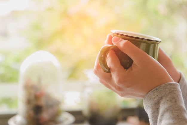 Woman hands holding hot cup of coffee or tea in morning