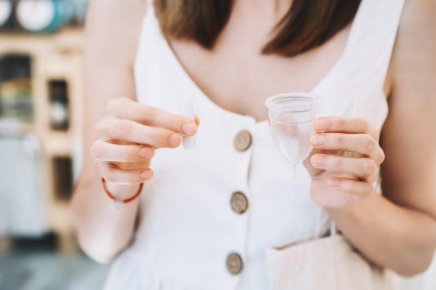 Woman hands holding menstrual cup and tampons different types of feminine period items