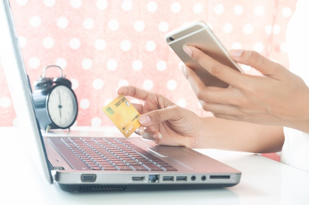 Woman hands holding mobile phone and plastic credit card. e-payment. online shopping