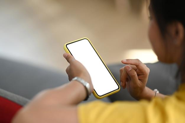 Руки женщины держа макет смартфона с пустым экраном.