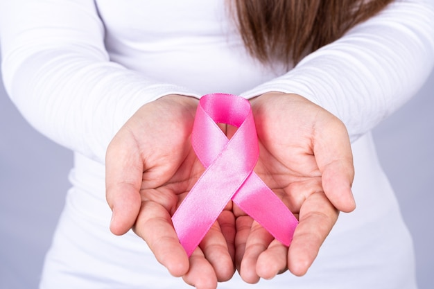 Woman hands holding pink breast cancer awareness ribbon.
