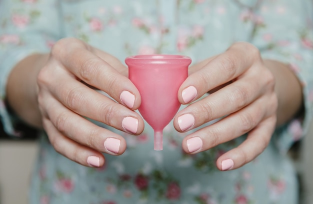 분홍색 생리컵을 들고 있는 여자 손. 현대 여성 친밀한 위생 개념입니다.