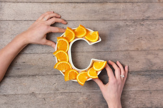 Woman hands holding plate in shape of letter c