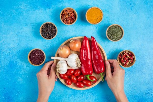 Mani della donna che tengono piatto di verdure.