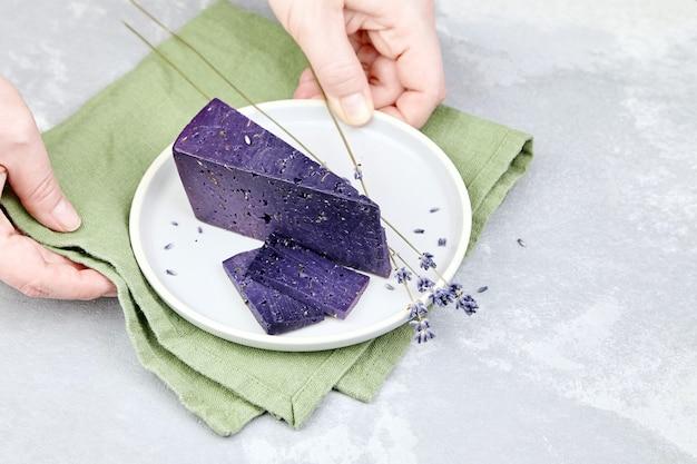 허브 재료와 화려한 라벤더 치즈의 조각으로 접시를 들고 여자 손