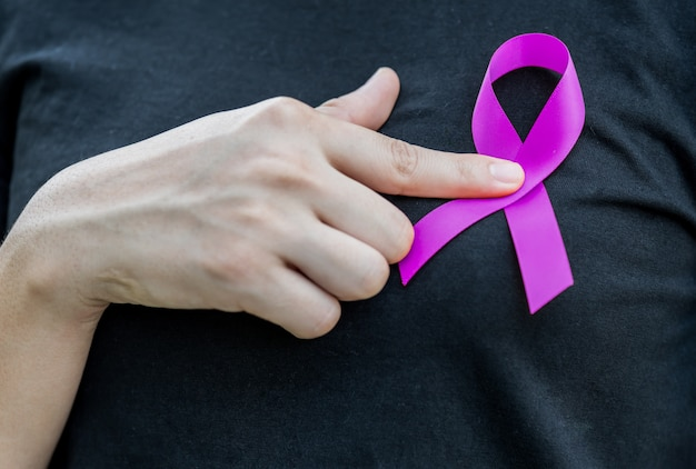 Woman hands holding purple cancer awareness ribbon.