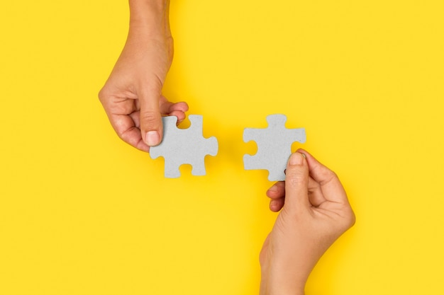 Woman hands holding puzzle pieces on a yellow background