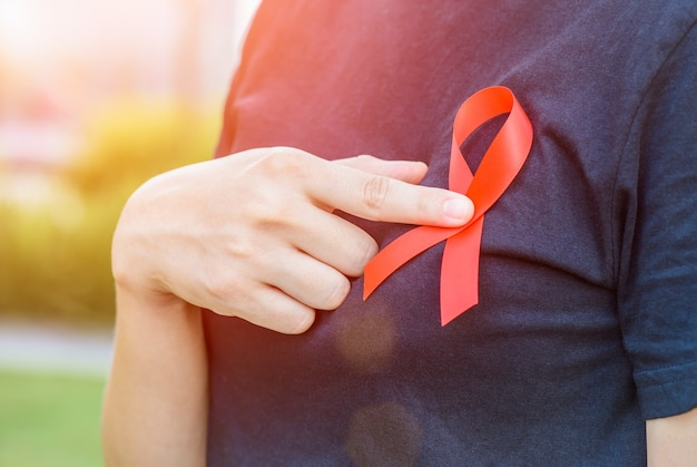 Woman hands holding red aids awareness ribbon.