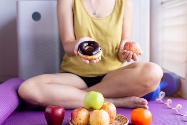 自宅で赤いリンゴと焼きチョコレートドーナツを保持している女性の手、健康的な食事、ダイエットの概念