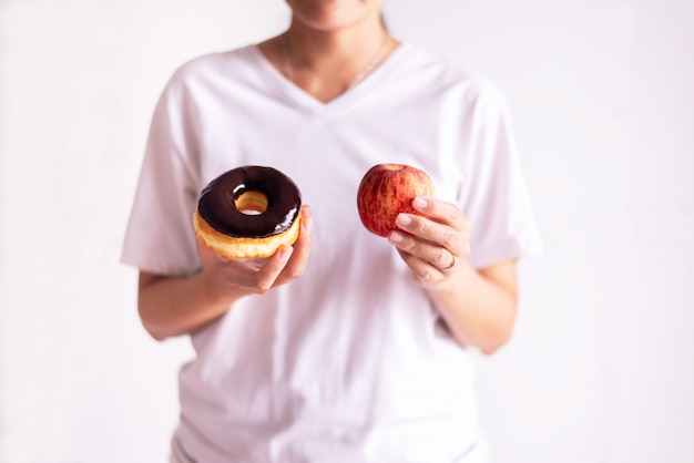 흰색 배경에 빨간 사과와 구운 초콜릿 도넛을 들고 있는 여성의 손, 건강한 식단, 다이어트 개념