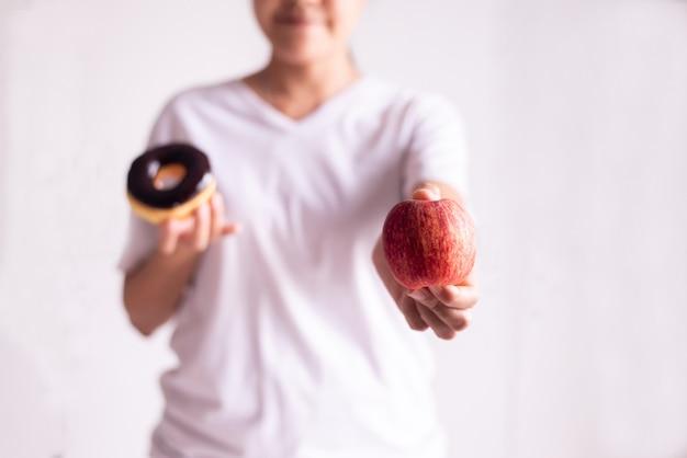 赤いリンゴと白い背景の上のチョコレートドーナツを保持している女性の手、健康的な食事、ダイエットの概念