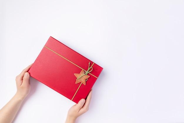 赤いクラフトペーパーギフトボックスを保持している女性の手