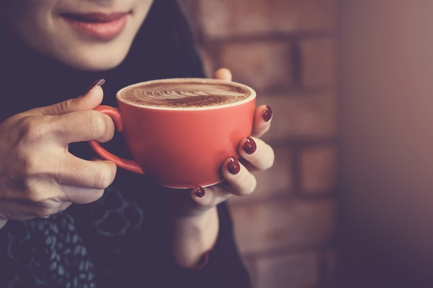 Woman hands holding red cup of coffee latte