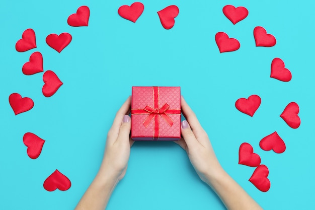 Woman hands holding red gift box on blue background with many hearts, copyspace. valentine's day greeting card, happy valentine day background. high quality photo