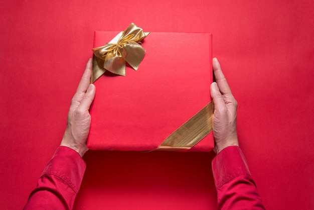 Woman hands holding red gift box with gold ribbon on red background, copy space