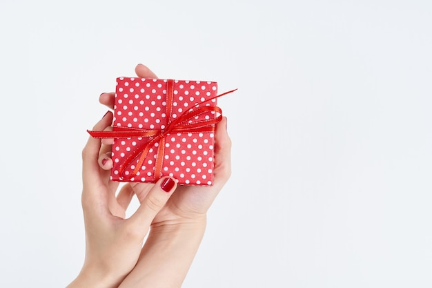 Woman hands holding red gift with ribbon, manicured hands with nail polish